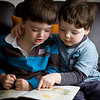 Alexander and Oliver reading together.  (Experimenting to emulate window-light. Setup: Photek Softlighter II (softliter) to the right with a 430EX and triggered by a 580EX II on the camera A:B ratio of 1:2 (Softlighter was very close to Oliver).  Canon 40D in Manual mode on ISO 200 at 1/200th second through the Canon 50mm f/1.4 lens@2.8)